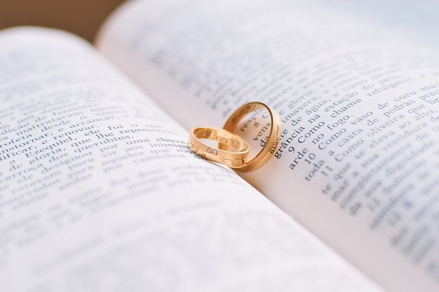 two gold wedding rings on open book