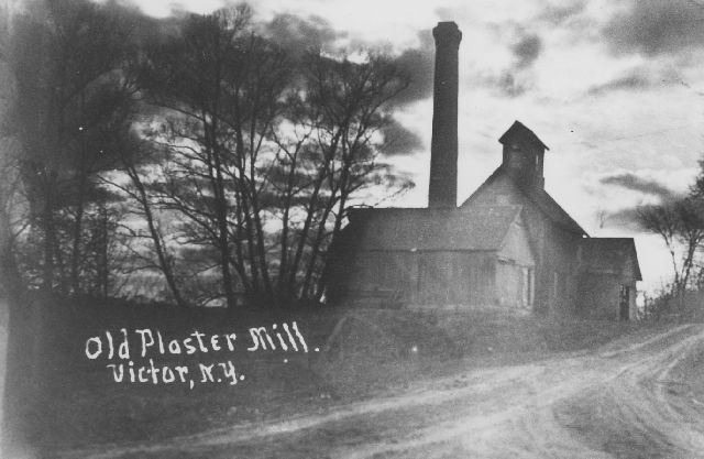 Wooden structure building of old plastermill on dirt road with smokestack