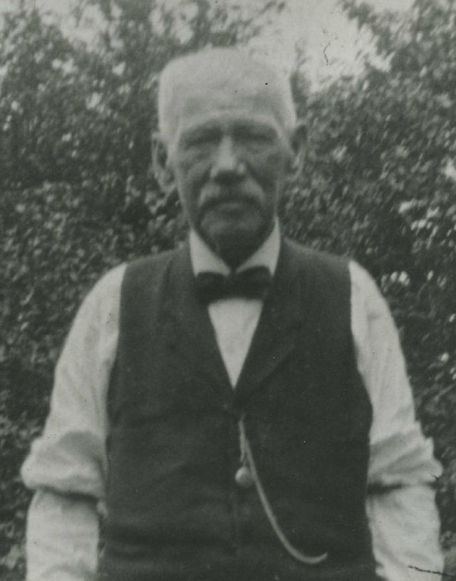 black and white photo of Alexander McCrahon white shirt and vest with watch and chain
