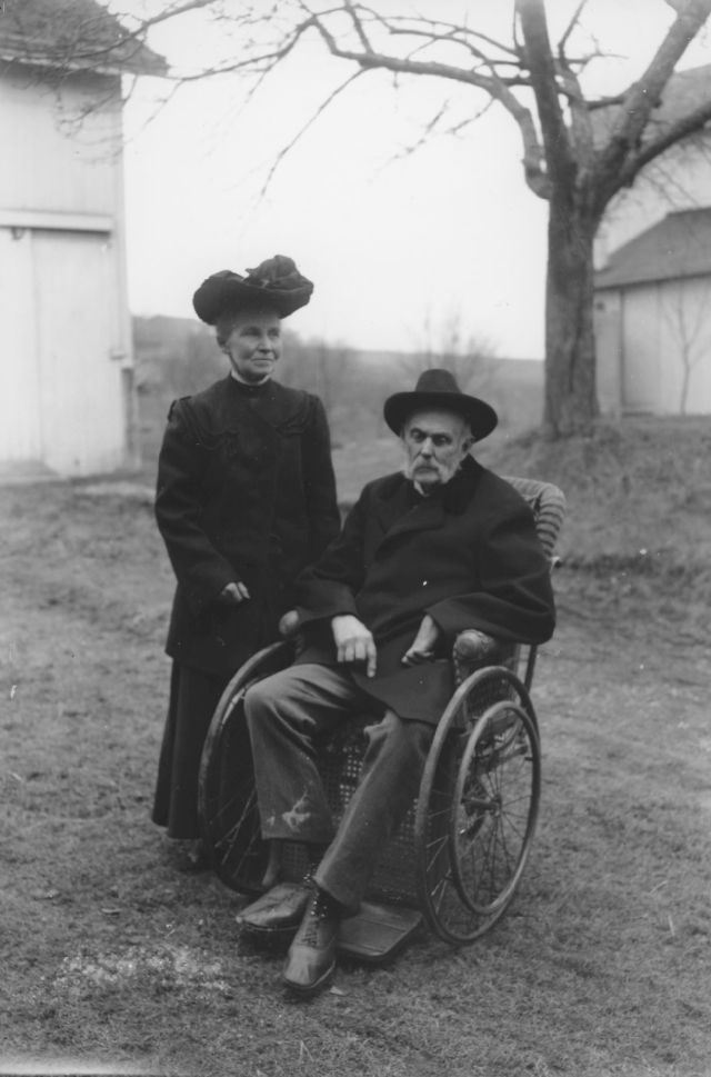 black and white photo of James Moore in wheelchair and wife Irene standing beside taken outside in f